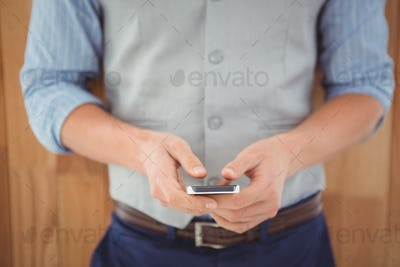 Mid section of businessman using mobile phone against wooden wall in office