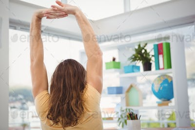Rear view of hipster stretching arms in office