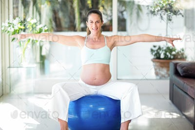 Portrait of pregnant woman with arms outstretched on ball at home