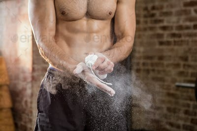 Midsection of muscular man applying chalk powder at the gym