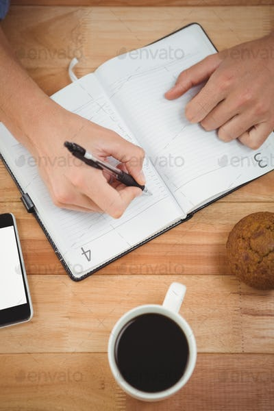 Cropped image of man writing on diary with muffin and coffee at desk in office
