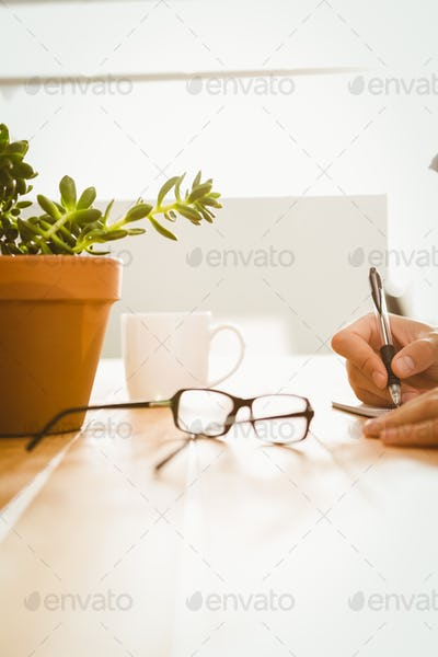 Cropped hand of man writing on book at desk in office
