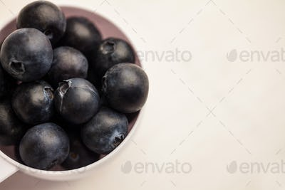 Portion cup of fresh blueberries on wooden table