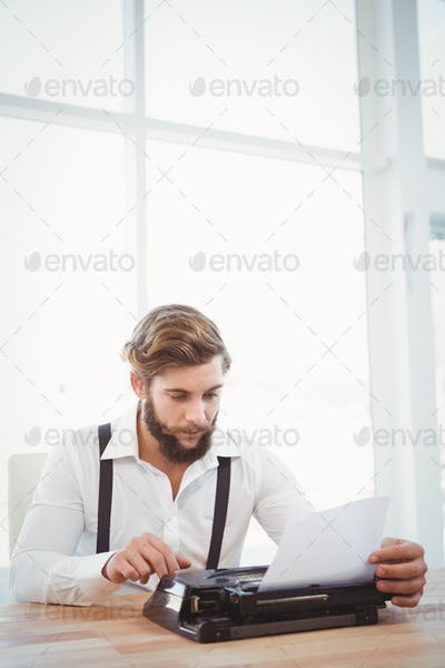 Hipster using typewriter at desk against window in office