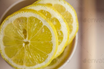 Portion cup of lemon slices on wooden table