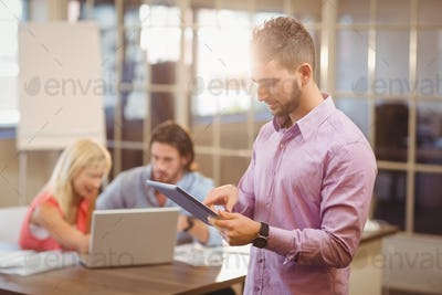 Businessman using digital tablet in office with colleagues on laptop in background