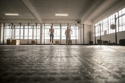 Two fit people start a running in crossfit gym