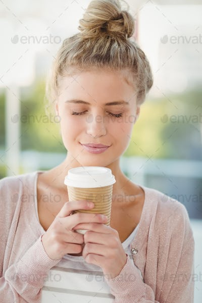 Tempted woman with eyes closed while holding coffee cup