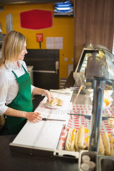 Female shop owner at display cabinet in bakery