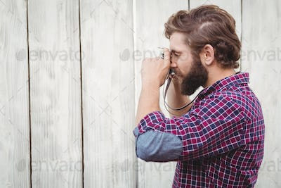 Side view of hipster photographing with camera against wooden wall