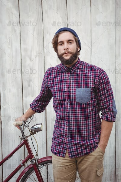 Portrait of confident hipster with bicycle against wooden fence