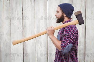 Side view of hipster with axe on shoulder against wooden fence