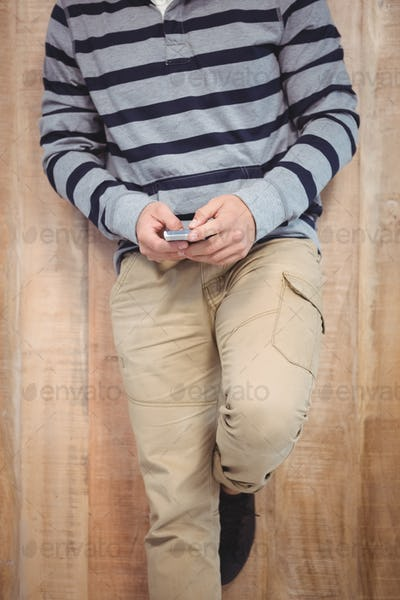 Low section of man using smartphone leaning against wooden wall