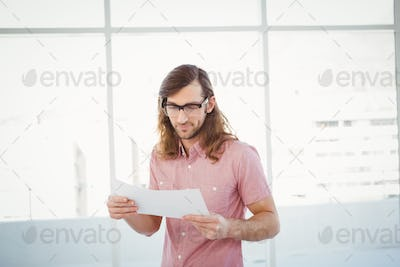 Confident hipster looking at documents standing against window in office