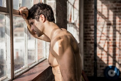 Shirtless man looking outside window at the gym