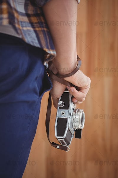 Cropped image of man holding camera against wooden wall in office