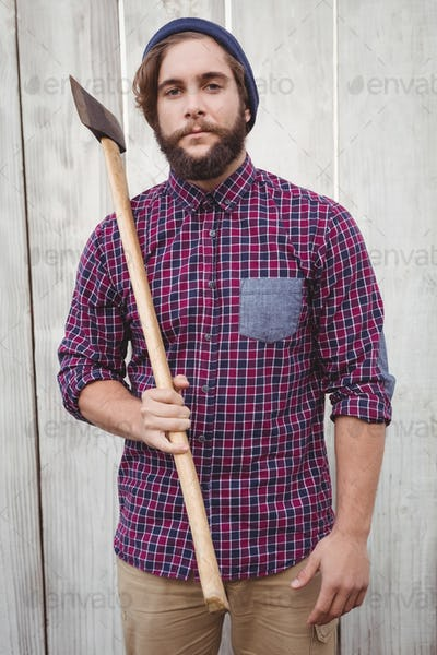 Portrait of hipster holding axe against wooden fence