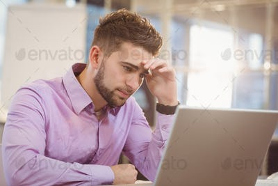 Worried businessman looking at laptop in office