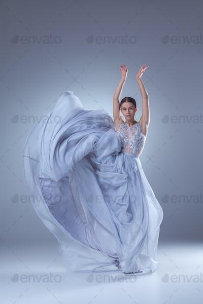The beautiful ballerina dancing in blue long dress