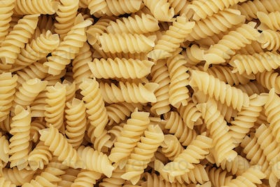 Close-Up Of Dry Uncooked Rotini Texture Background