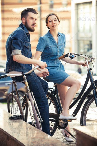 Young couple sitting on a bicycle opposite city