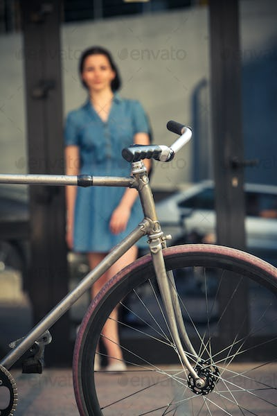 Young girl with a bicycle opposite city