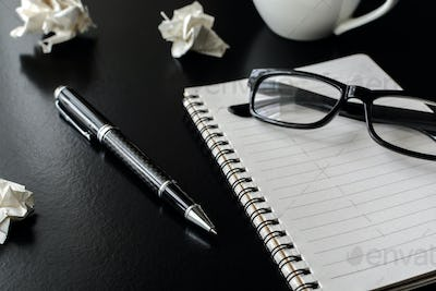 Crumpled paper balls with eye glasses and notebook