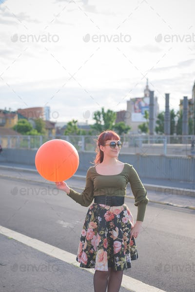 young handsome redhead woman playing with balloon