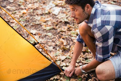 Handsome man setting up a tent