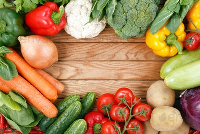 Vegetables on wood background with space for text.