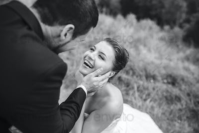 groom gently touches the face of his bride