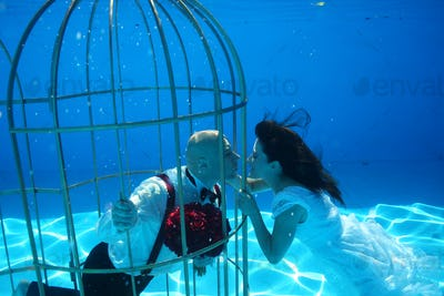Beautiful bride and groom having fun underwater in birdcage