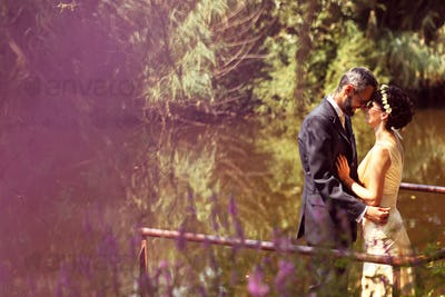 Beautiful bride and groom embracing and kissing in field