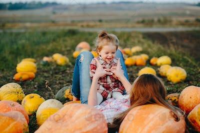 mother and daughter lie between pumpkins