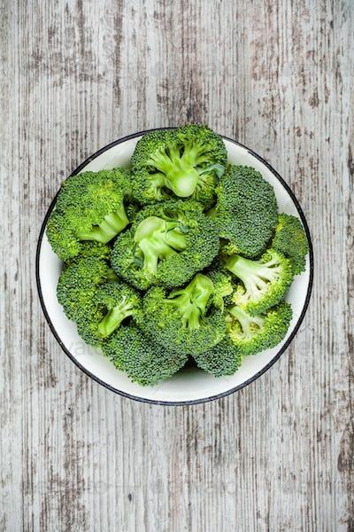 Fresh raw organic broccoli in bowl on a wooden background