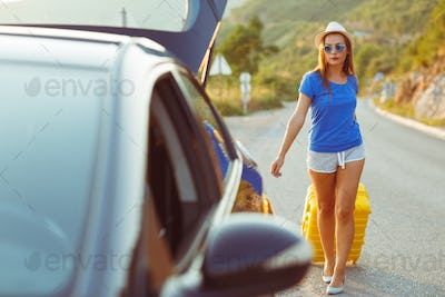 Woman with a yellow suitcase goes to a car parked on the roadsid