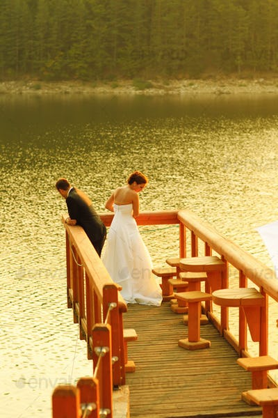 Beautiful bride and groom embracing near a lake