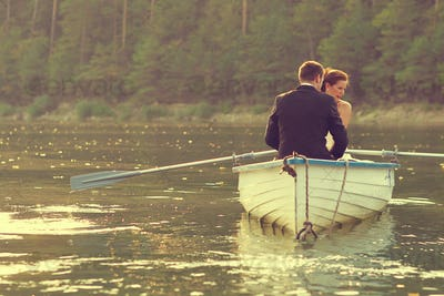 Beautiful bride and groom in a boat on the lake