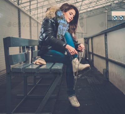 Cheerful girl putting on skates  on ice skating rink