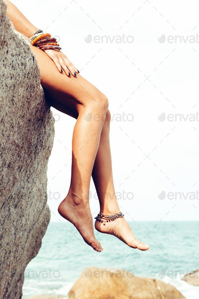Girl posing on rocks alone on ocean seashore