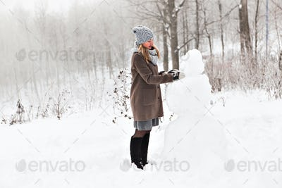Happy young woman  and  snowman