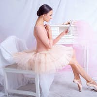 Professional ballet dancer looking in the mirror on pink