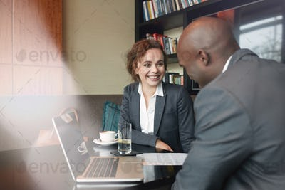 Two young businesspeople meeting in coffee shop