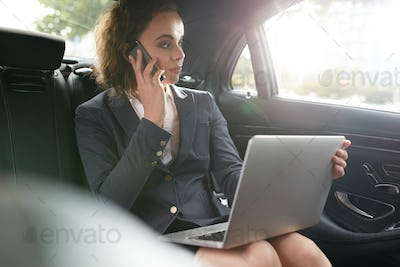 Female executive travelling to work in luxury car