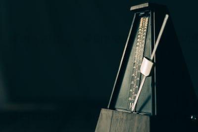 Vintage metronome, on a dark background.