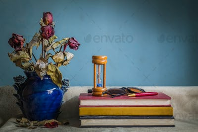 Books and a vase of dried flowers