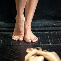 Close-up ballerina's legs and pointes on the black wooden floor