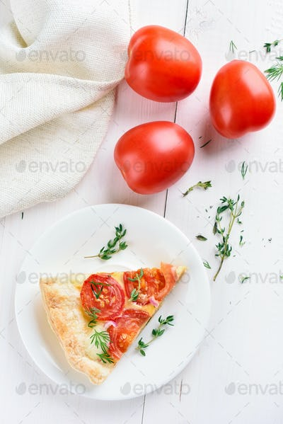 Pie slice and fresh tomatoes