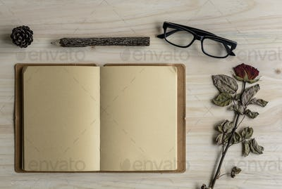 Blank note book with eye glasses on wooden desk