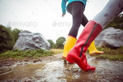 Women splashing in muddy puddles in the countryside
